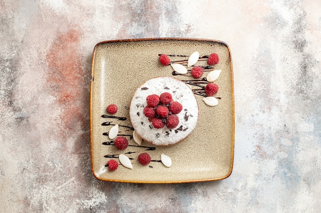 Horizontal view of freshly baked cake with raspberries for babies on a brown tray on white table