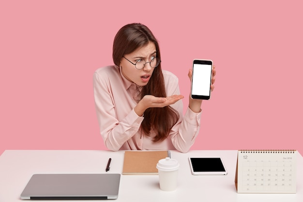 Horizontal view of frustrated woman demonstrates something on empty screen of mobile phone