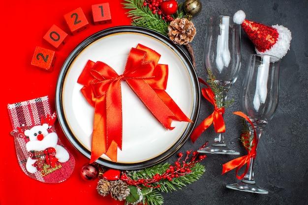 Vista orizzontale del regalo con nastro rosso piatti per la cena accessori decorativi rami di abete calza di natale calici di vetro cappello di babbo natale sul tavolo scuro