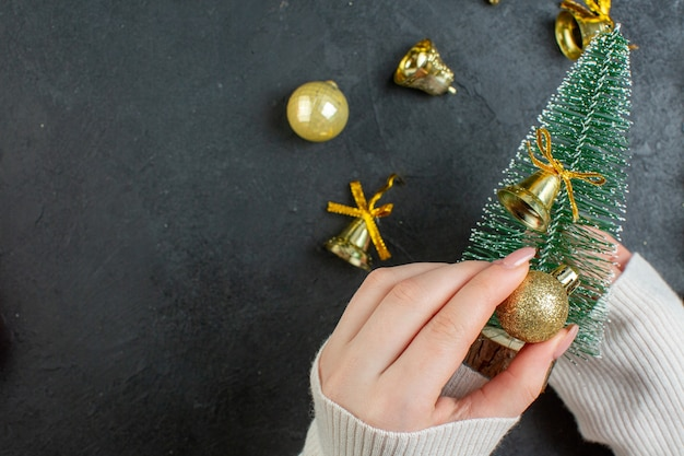 Vista orizzontale della mano che tiene l'albero di natale e gli accessori della decorazione sul tavolo scuro