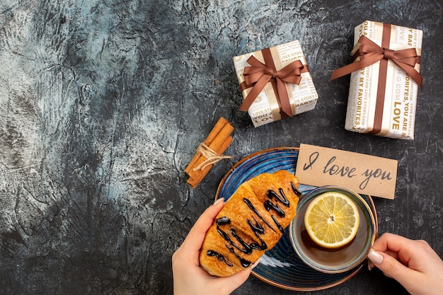 Horizontal view of hand holding a cup of black tea delicious croisasant i love you writing on a tray cinnamon limes gifts on dark background