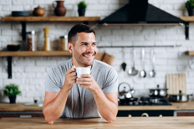 Horizontal view of the handsome man sitting on the chair leaned on table, smiling and looking away while drinking coffee. image at the cozy kitchen