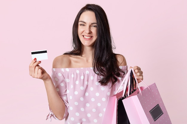 Horizontal view of happy brunette woman with pleased expression, carries shopping bags and plastic card, rejoices having enough money