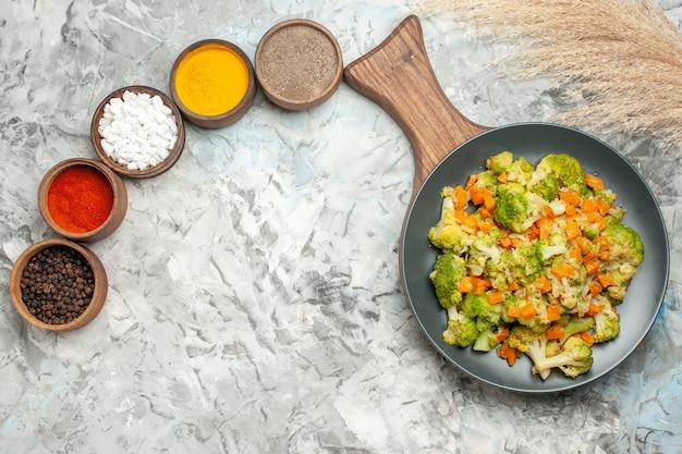 Vista orizzontale di una sana insalata di verdure diverse spezie sul tavolo bianco