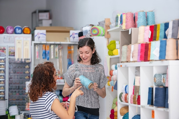 Horizontal view of help assistant on a retail shop helping a woman to buy a ball of blue yarn