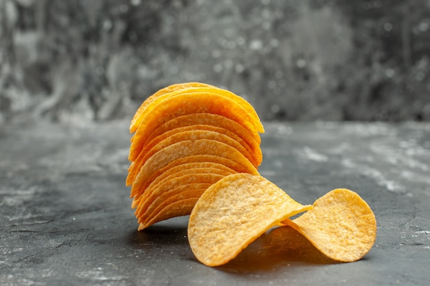 Horizontal view of homemade stacked potato chips on gray table