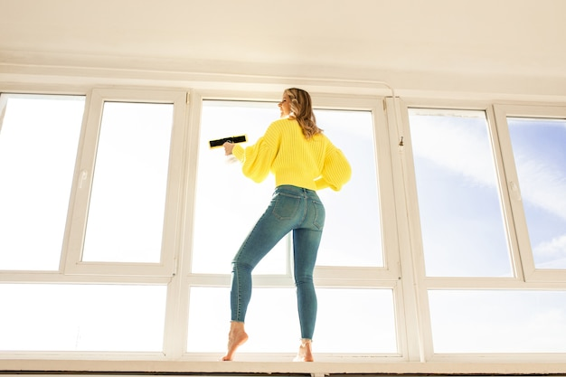 Horizontal view housewife washes windows while standing on the windowsill concept of cleanliness and sterility in house apartament cleaning