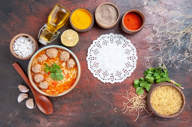 Vista orizzontale della zuppa di polpette con pasta in una ciotola marrone cucchiaio di limone un mucchio di spezie verdi diverse e pasta tovagliolo bottiglia di olio sul tavolo scuro