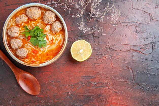 Vista orizzontale della zuppa di polpette con noodles in una ciotola marrone cucchiaio di limone sul lato destro su sfondo scuro