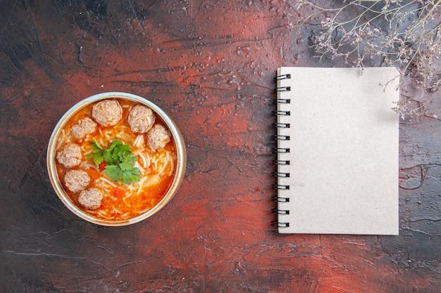 Vista orizzontale della zuppa di polpette con noodles in una ciotola marrone e taccuino su sfondo scuro