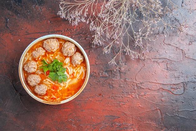 Vista orizzontale della zuppa di polpette con noodles in una ciotola marrone sul lato destro dello sfondo scuro
