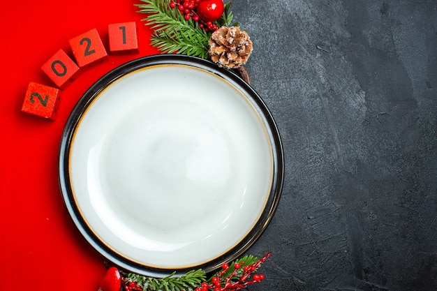 Horizontal view of new year background with dinner plate decoration accessories fir branches and numbers on a red napkin on a black table