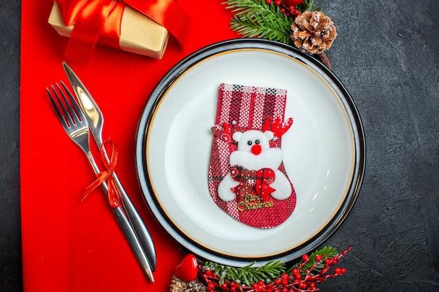 Vista orizzontale del nuovo anno sfondo con calzino sulla piastra della cena set di posate decorazione accessori rami di abete accanto a un regalo su un tovagliolo rosso