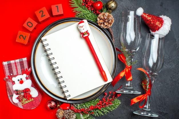 Vista orizzontale del taccuino sui piatti della cena accessori decorativi rami di abete calza di natale calici di vetro sul tavolo scuro