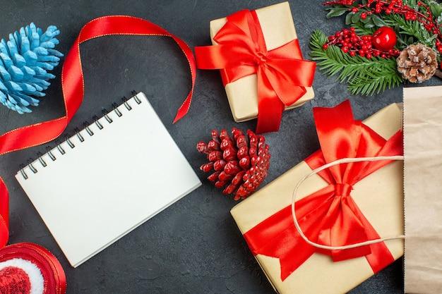 Горизонтальный вид рулона красных хвойных шишек и подарочных еловых веток рядом с ноутбуком на темном фоне