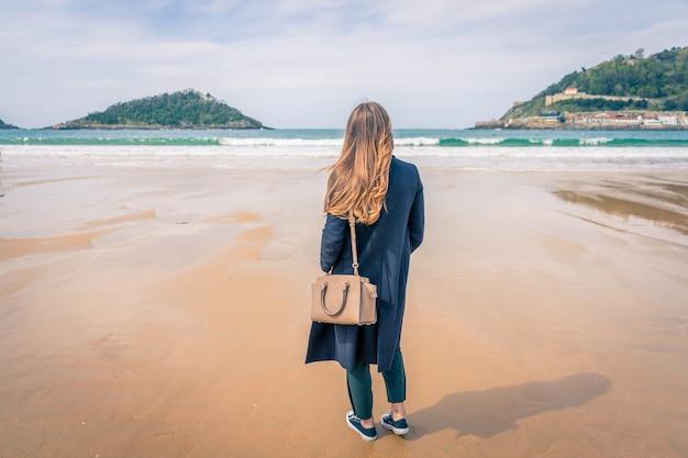 美しい砂浜、スペインに立っている若い女性の水平方向のビュー