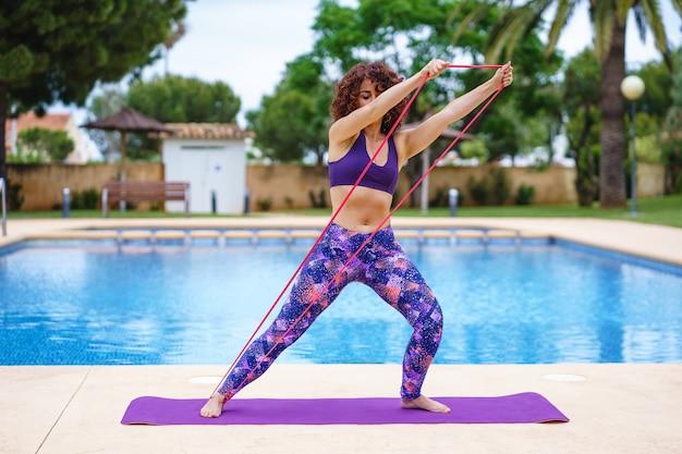 Горизонтальный вид кавказской женщины, разрабатывающей эластичность рядом с бассейном. фитнес-образ жизни, упражнения и здоровые привычки на открытом воздухе.