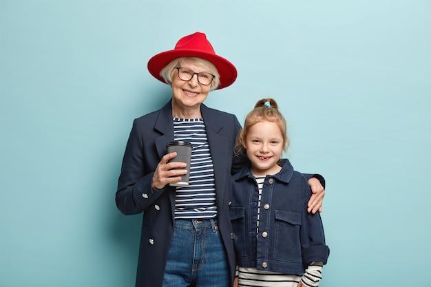 쾌활한 할머니의 가로보기는 빨간색 세련된 모자, 검은 재킷을 착용