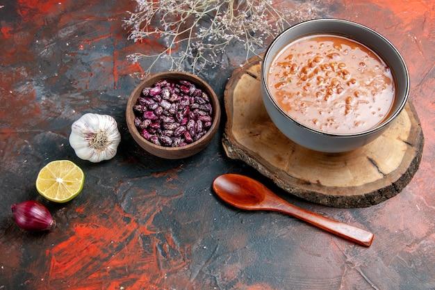混合色のテーブルの上の木製トレイオイルボトル豆ニンニク玉ねぎとレモンの青いボウルの古典的なトマトスープの水平方向のビュー