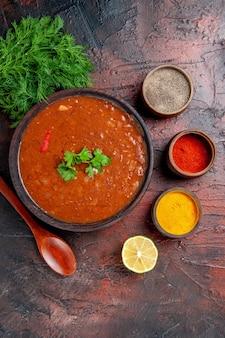 Горизонтальный вид классического томатного супа в коричневой миске и разных специй на столе смешанного цвета