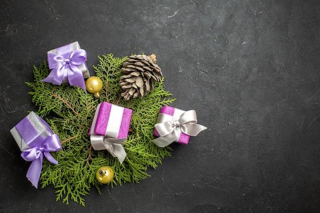 カラフルな新年の贈り物の装飾アクセサリーと暗い背景の針葉樹の円錐形の水平方向のビュー