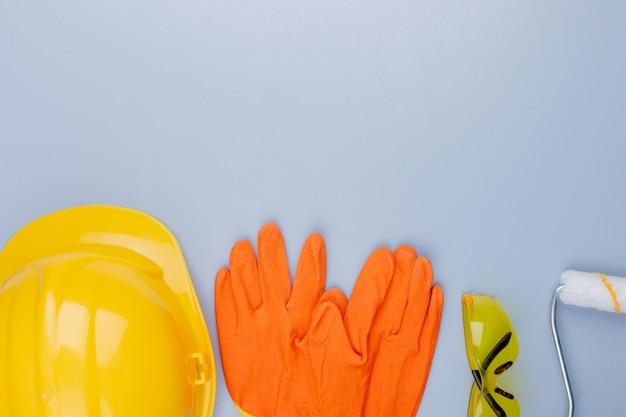 Горизонтальный вид строительных инструментов как защитных шлемов, перчаток, защитных очков и малярного валика на сером фоне с копией пространства