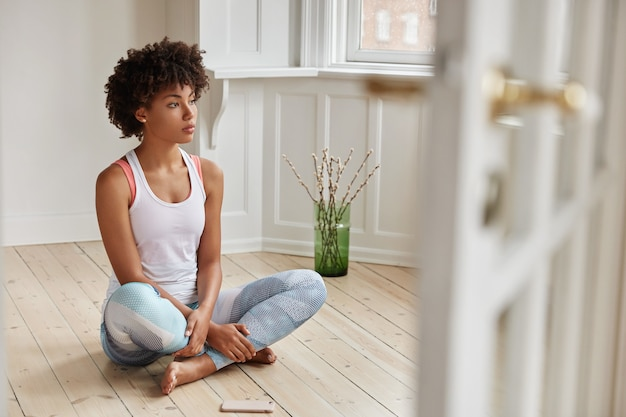 瞑想的な暗い肌の女性の水平方向のビューは、足を折りたたんで、カジュアルな服を着て、朝のトレーニングの後に休憩します