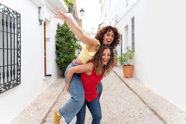 おんぶを笑っているカップルのガールフレンドの水平方向のビュー。友情の夏のコンセプト