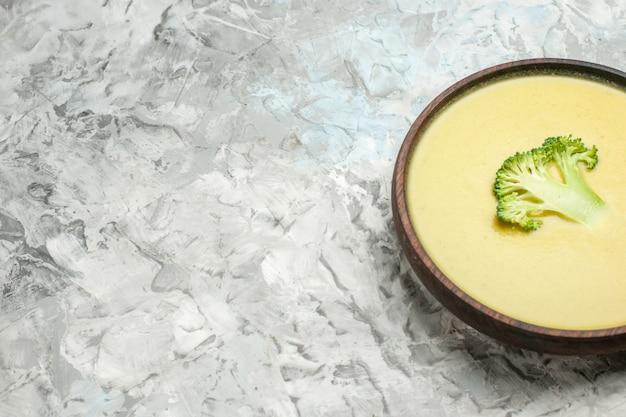 白いテーブルの上の茶色のボウルにブロッコリースープのクリームの水平方向のビュー