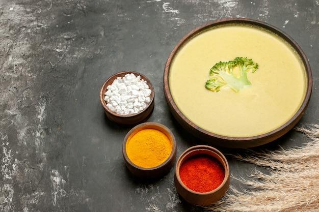 茶色のボウルにクリーミーなブロッコリースープと灰色のテーブルにさまざまなスパイスの水平方向のビュー