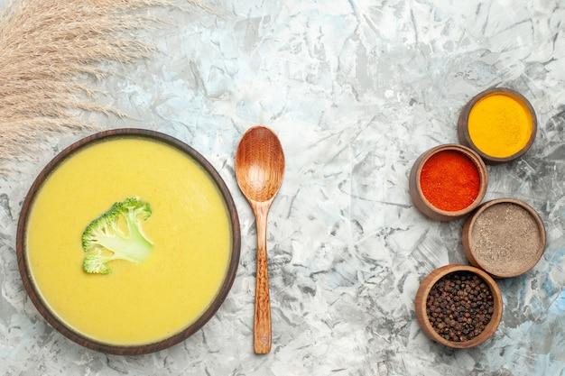 Горизонтальный вид сливочного супа из брокколи в коричневой миске и различных специй на сером столе