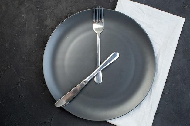 여유 공간이 있는 어두운 색 배경에 흰색 수건에 검정 접시에 설정된 칼 붙이의 수평 보기