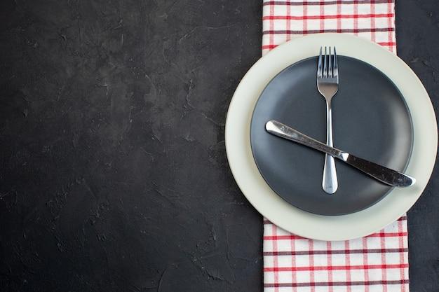 검은색 바탕에 여유 공간이 있는 왼쪽에 빨간색 벗겨진 수건에 어두운 회색 색상과 흰색 빈 접시에 설정된 칼 붙이의 수평 보기