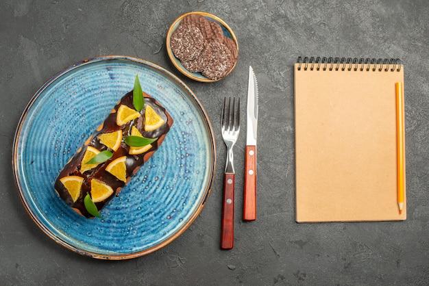 Горизонтальный вид вкусного торта и печенья с вилкой и ножом рядом с блокнотом на черном столе