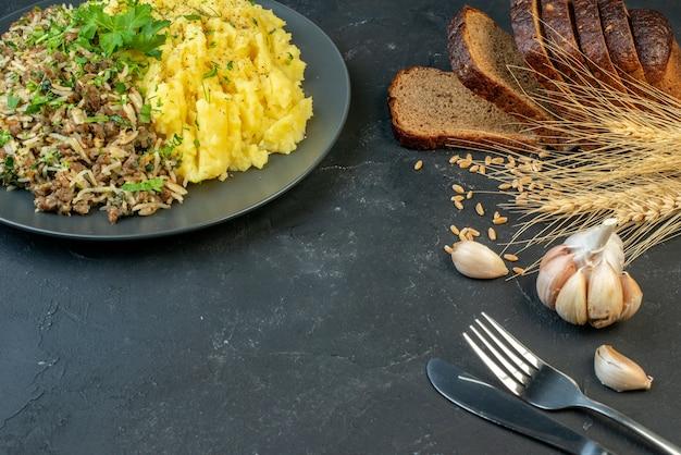 Горизонтальный вид вкусного ужина с мясом и картофельным пюре на серой тарелке, ломтики хлеба, набор столовых приборов с чесночным шипом на черном фоне