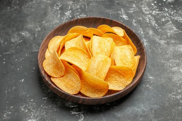 Горизонтальный вид вкусных домашних картофельных чипсов на коричневой тарелке на сером столе
