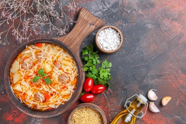 나무 커팅 보드에 닭고기를 넣은 맛있는 국수 수프의 수평 보기 어두운 배경에 녹색 토마토 한 다발
