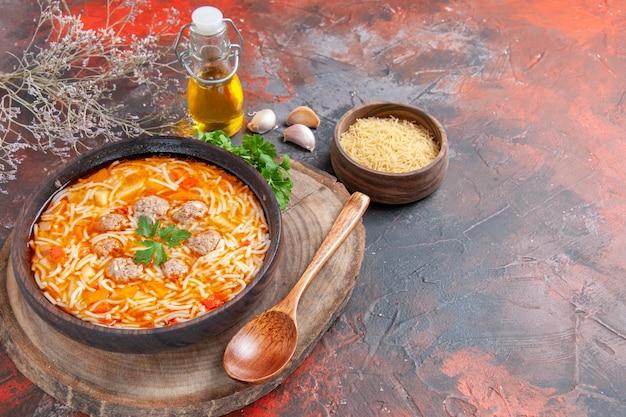 어두운 배경에 나무 커팅 보드 그린 스푼 오일 병 마늘에 닭고기와 함께 맛있는 국수 수프의 수평 보기