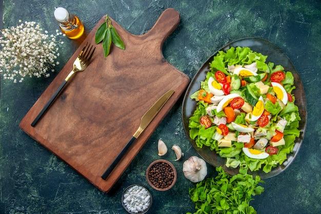 木製のまな板にセットされた多くの新鮮な食材スパイスオイルボトルニンニクカトラリーとおいしいサラダの水平方向のビュー