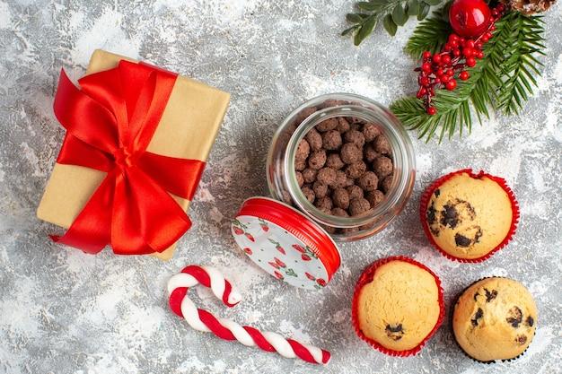 氷の表面に赤いリボンとギフトの横にあるガラスの鍋とモミの枝においしい小さなカップケーキとチョコレートの水平方向のビュー