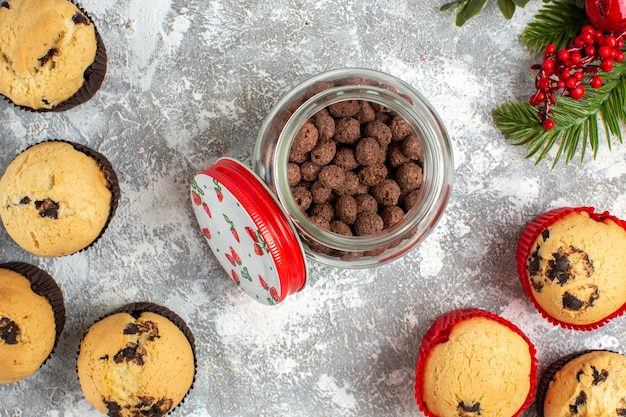 ガラスの鍋と氷の表面のモミの枝においしい小さなカップケーキとチョコレートの水平方向のビュー