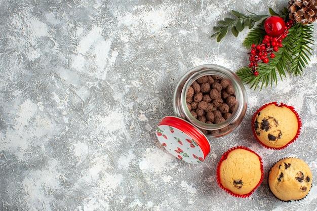 氷の表面の左側にあるガラスの鍋とモミの枝の中のおいしい小さなカップケーキとチョコレートの水平方向のビュー