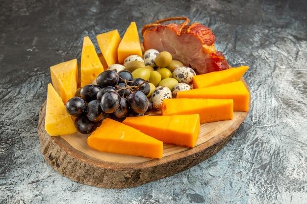 氷の背景の上の茶色のトレイに果物や食べ物を含むおいしいスナックの水平方向のビュー