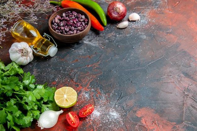 混合色のテーブルに食品と豆のオイルボトルと緑のレモントマトの束と夕食の準備の水平方向のビュー