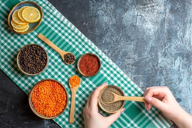 緑のはがしたタオルの上に、さまざまなピーマンと黄色いエンドウ豆を使った夕食の準備の水平方向の眺め
