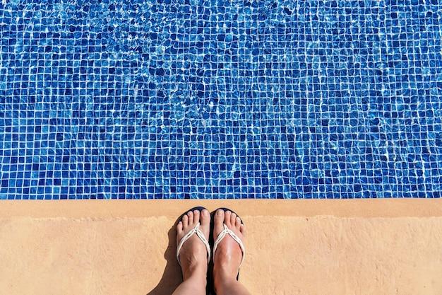 スイミングプールのビーチサンダルで足の水平方向のビュー。概念的な夏休みの概念。