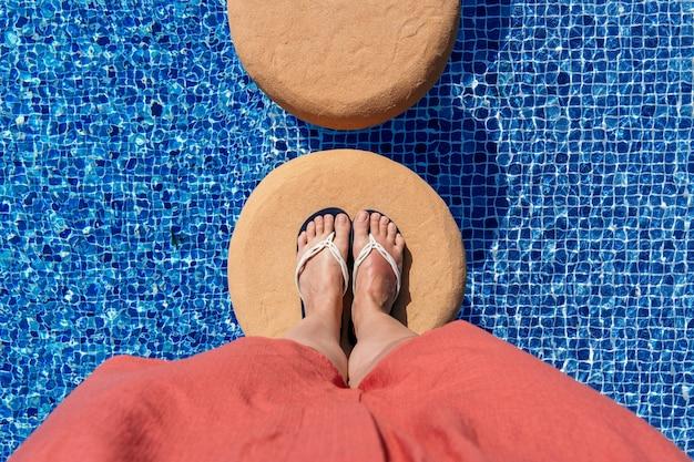 スイミングプールのビーチサンダルで足の水平方向のビュー。概念的な晴れた夏の休日の概念。