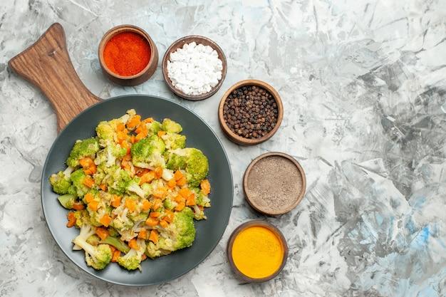 白いテーブルの上の木製まな板に新鮮で健康的な野菜サラダの水平方向のビュー