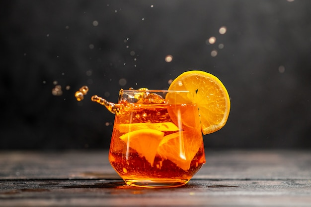 暗いテーブルの上のオレンジ色のライムとガラスの新鮮なおいしいジュースの水平方向のビュー