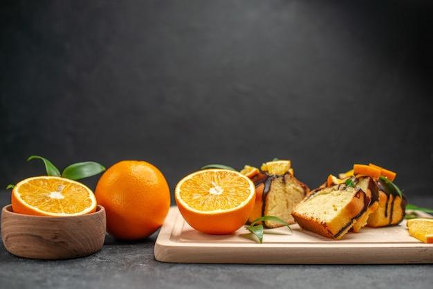 Горизонтальный вид свежих ломтиков лимона и свежеиспеченных нарезанных ломтиков торта на темном столе